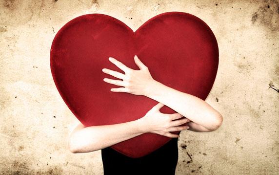 Uma mulher abraçando um grande coração