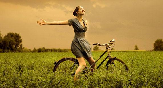 Uma mulher feliz, no campo, com sua bicicleta.