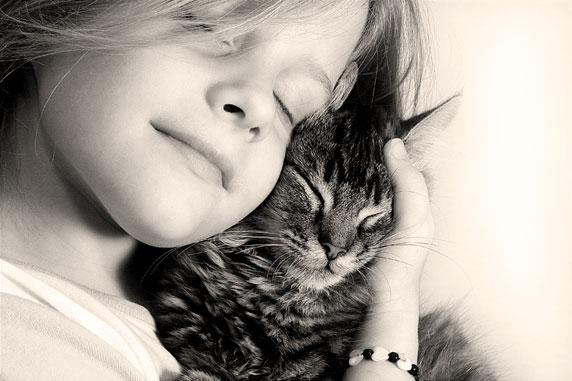 Foto de uma menina feliz, com seu gato.